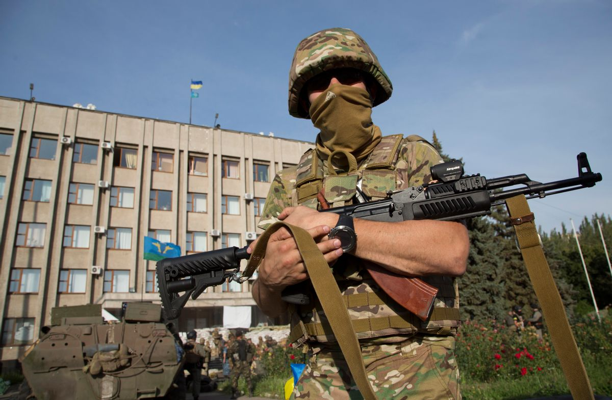 An Ukrainian government army soldier stands in front of the government building with a Ukrainian flag on the roof in the city of Slovyansk. (AP/Dmitry Lovetsky)