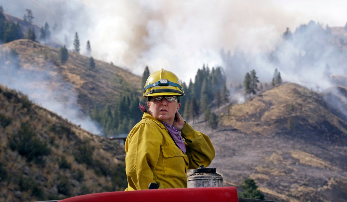 Firefighter Kathleen Calvin looks around as she sits atop her fire truck while waiting to begin work as smoke from a wildfire fills the sky behind Saturday, July 19, 2014, in Winthrop, Wash. (AP Photo/Elaine Thompson)