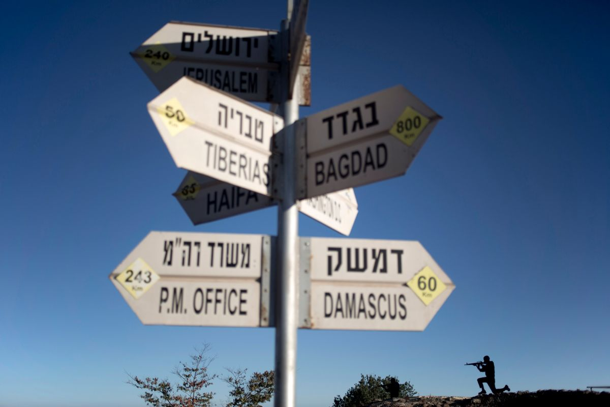 A sign showing the direction and distance to cities stands as a metal board in the shape of a gunman is placed on an old bunker at an observation point on Mt. Bental in the Israeli controlled Golan Heights, overlooking the border with Syria, Thursday, Aug. 28, 2014. (AP Photo/Ariel Schalit) (AP)