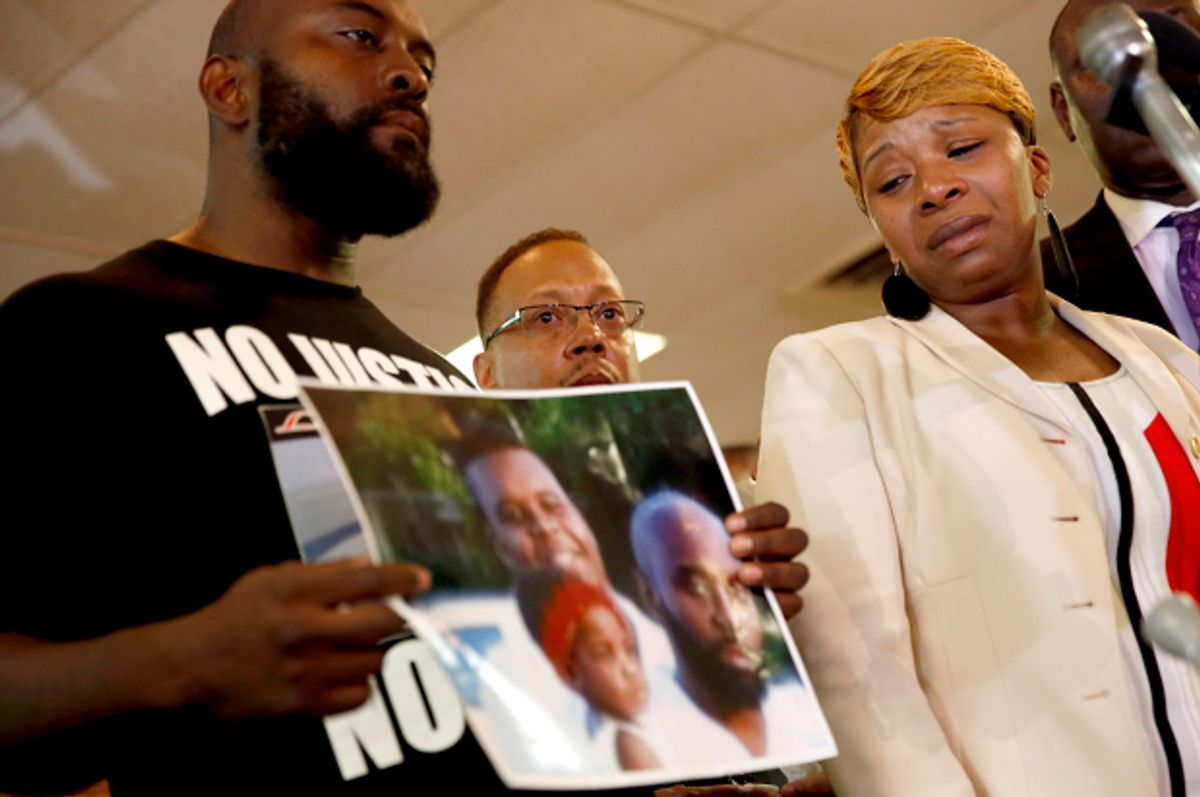 Lesley McSpadden, right, the mother of Michael Brown, watches as Brown's father, Michael Brown Sr., holds up a family picture, Aug. 11, 2014, in Ferguson, Mo.          (AP/Jeff Roberson)