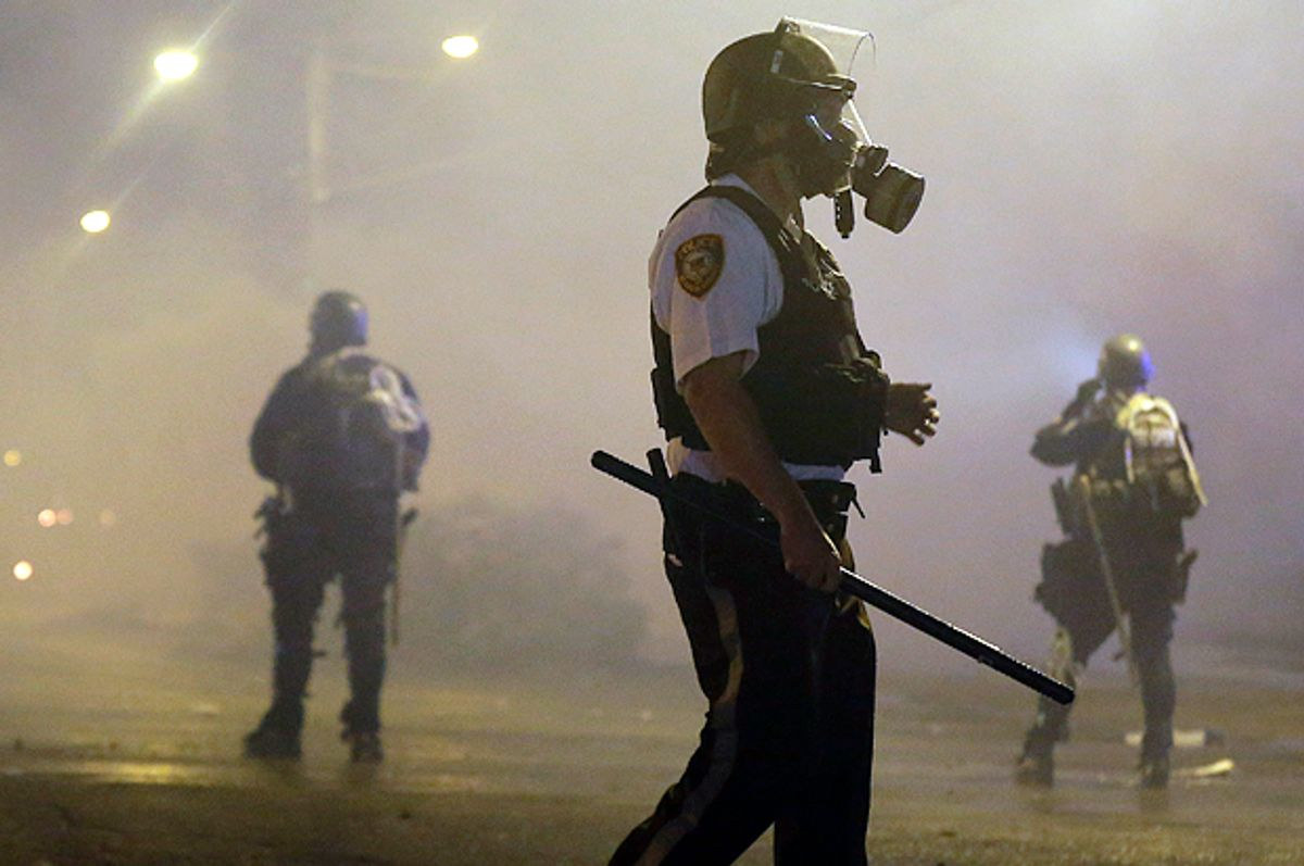 Law enforcement officers wait to advance Sunday, Aug. 17, 2014, after firing tear gas to disperse a crowd in Ferguson, Mo.                     (AP/Charlie Riedel)