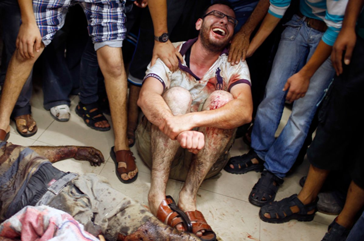 A Palestinian mourns next to the body of a man, who medics said was killed by Israeli shelling near a market in Shejaia, at a hospital in Gaza City, July 30, 2014.           (Reuters/Mohammed Salem)