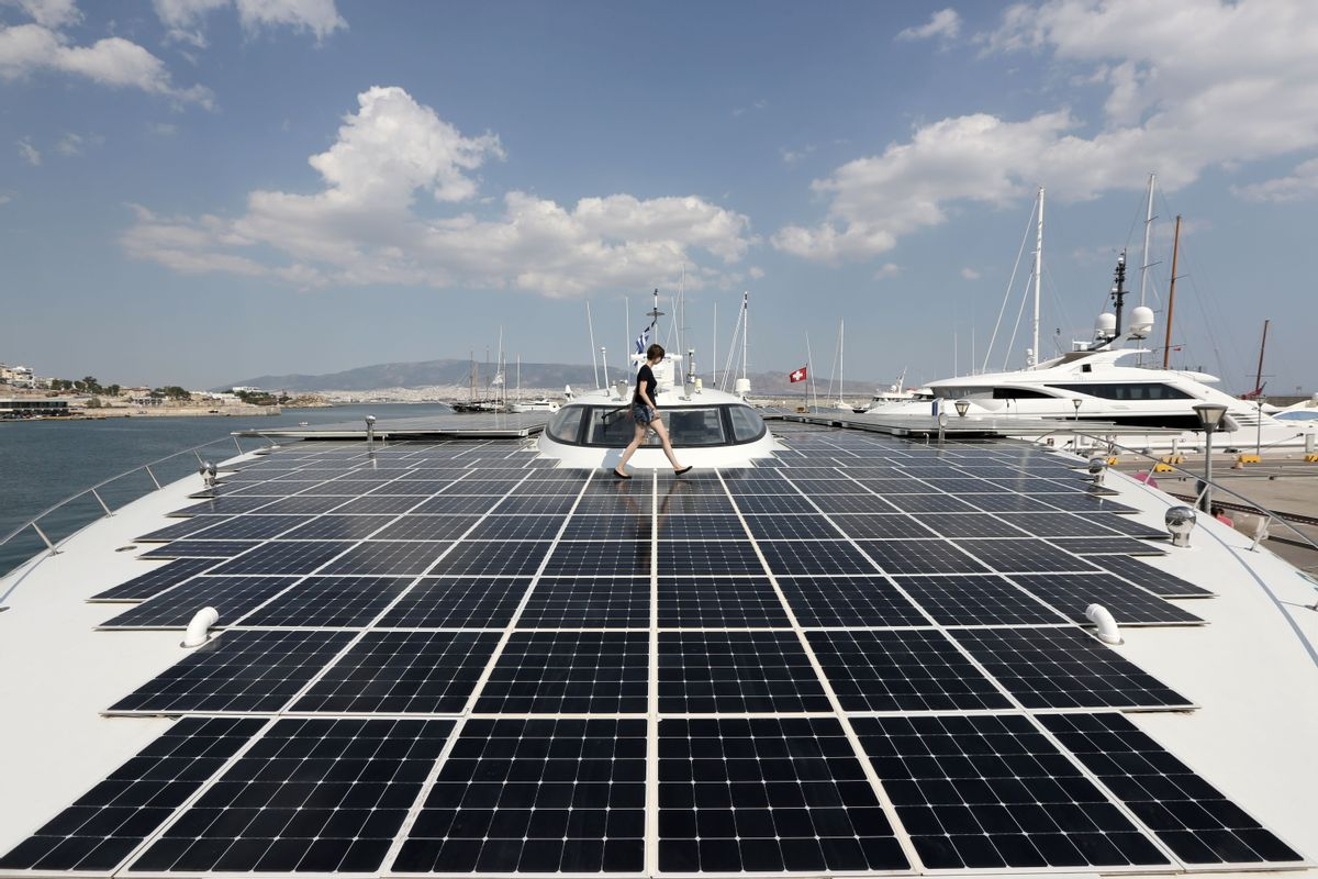 PlanetSolar press officer Julia Tames walks across the deck of the MS Turanor PlanetSolar, the world's largest solar-powered boat, moored at Zea Harbor, in Athens, on Tuesday Aug. 5, 2014. The 35-meter (115-foot) vessel is in Greece to take part in a Swiss-Greek underwater archaeology project to survey the seabed off a major prehistoric site, in hope of finding traces of what could be one of the earliest villages in Europe. (AP Photo/Thanassis Stavrakis) (AP)
