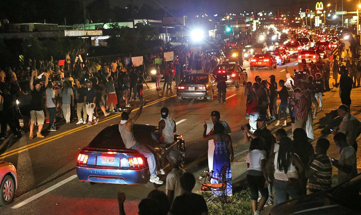 Many people drove down the street honking their horns, raising their arms, and holding signs on W. Florissant in Ferguson on Thursday evening, Aug. 14, 2014, as some demonstrators stood in the middle of the street.  (AP Photo/St. Louis Post-Dispatch, J.B. Forbes))