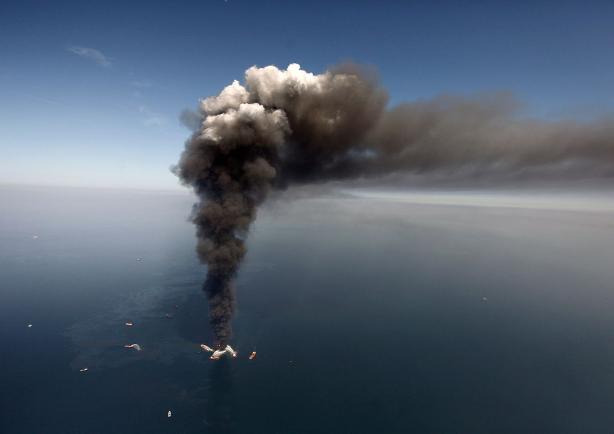 In this Wednesday, April 21, 2010 file photo, oil can be seen in the Gulf of Mexico, more than 50 miles southeast of Venice on Louisiana's tip, as a large plume of smoke rises from fires on BP's Deepwater Horizon offshore oil rig. (AP Photo/Gerald Herbert, File)