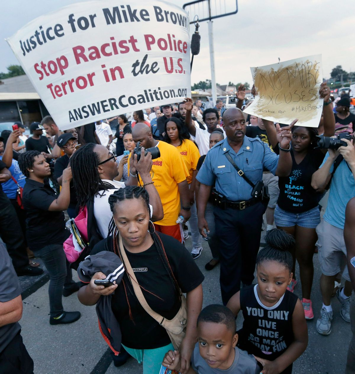 In this Aug, 16, 2014 file photo, Missouri Highway Patrol Capt. Ron Johnson walks among people protesting the police shooting death of Michael Brown a week ago in Ferguson, Mo. The Ferguson City Council, set to meet Tuesday, Sept. 9, 2014, for the first time since the fatal shooting of Brown, said it plans to establish a review board to help guide the police department and make other changes aimed at improving community relations.   (AP/Charlie Riedel)