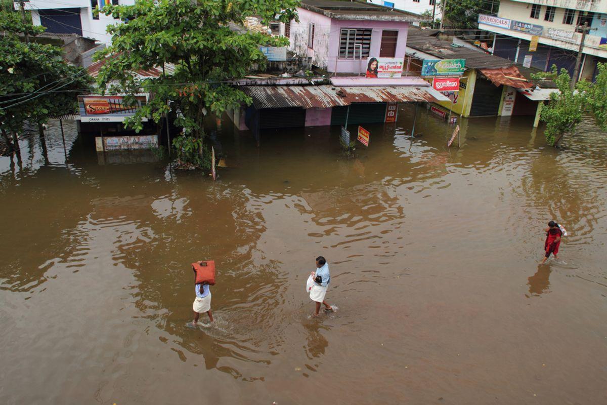 Unidentified people walk on the flood water on June 26,2013 in Kuttanad, India. (AJP/Shutterstock)