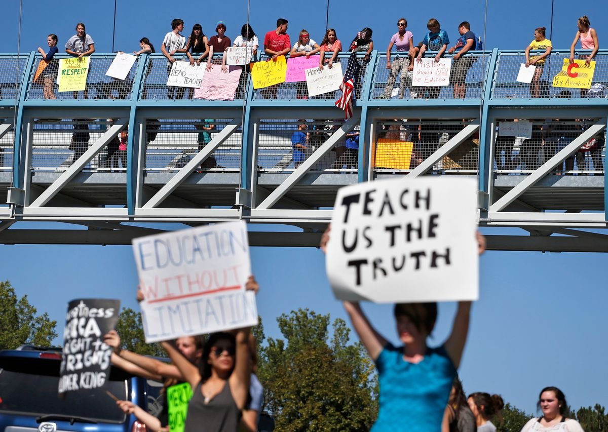Students line a busy intersection and overpass protesting against a Jefferson County School Board proposal to emphasize patriotism and downplay civil unrest in the teaching of U.S. history, in the Denver suburb of Littleton, Colo., Thursday, Sept. 25, 2014. Several hundred students walked out of class Thursday in the fourth straight day of protests in Jefferson County. (AP Photo/Brennan Linsley)  (AP)