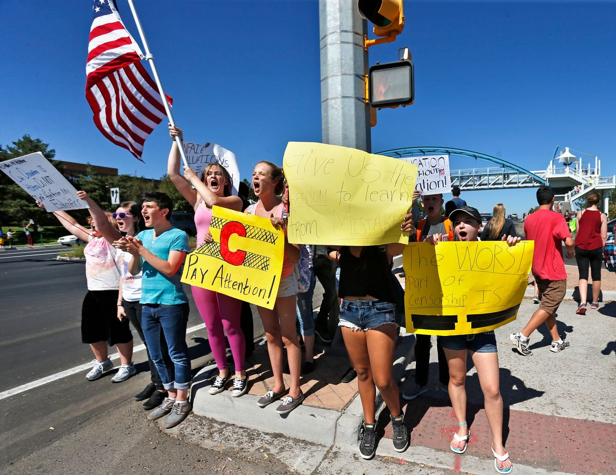 Students line a busy intersection protesting against a Jefferson County School Board proposal to emphasize patriotism and downplay civil unrest in the teaching of U.S. history, in the Denver suburb of Littleton,Thursday, Sept. 25, 2014. Several hundred students walked out of class Thursday in the fourth straight day of protests in Jefferson County.  (AP Photo/Brennan Linsley)
