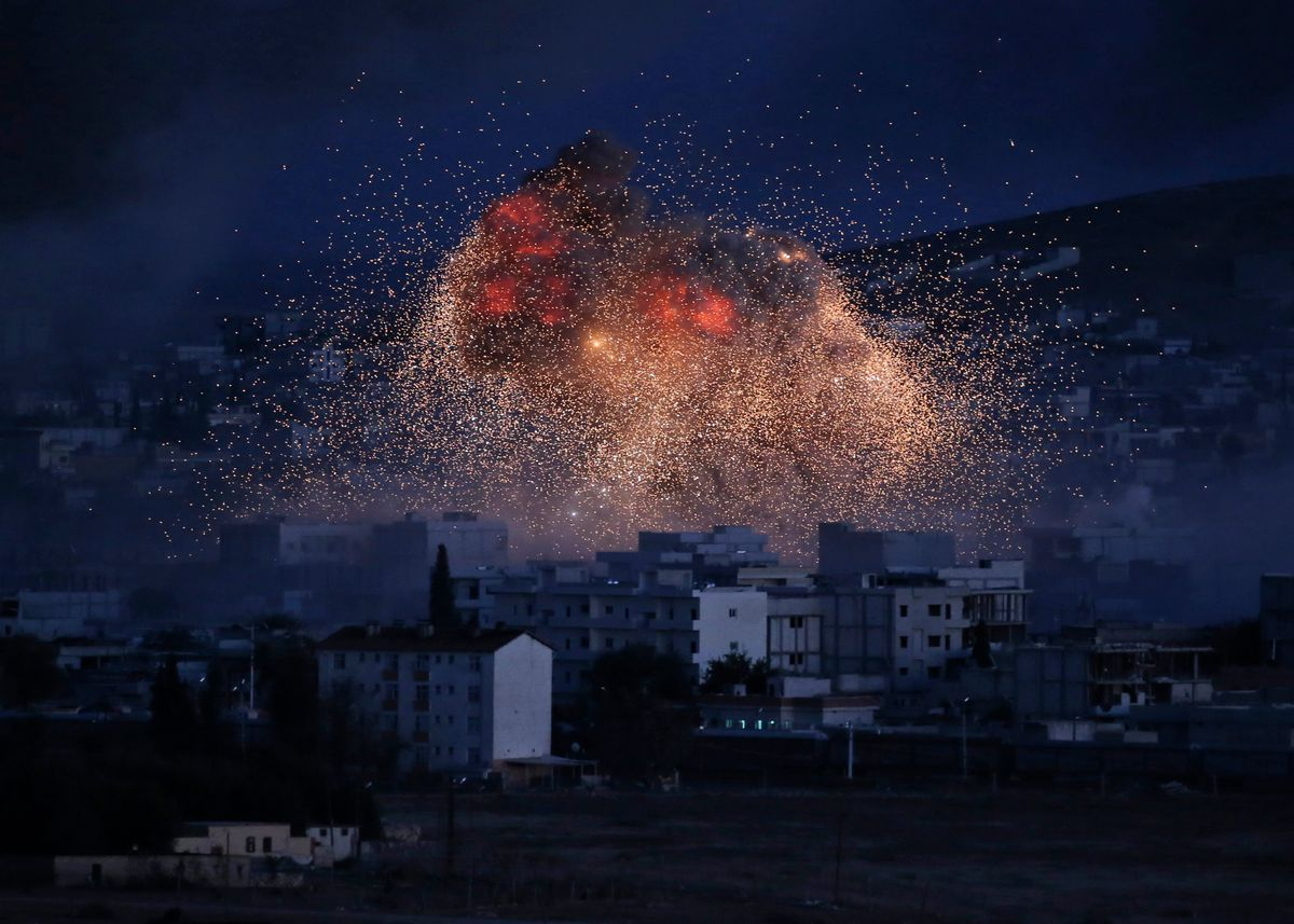 AP10ThingsToSee - Thick smoke and flames from an airstrike by the U.S.-led coalition rise in Kobani, Syria, as seen from a hilltop on the outskirts of Suruc, at the Turkey-Syria border, Monday, Oct. 20, 2014. Kobani, also known as Ayn Arab, and its surrounding areas, has been under assault by extremists of the Islamic State group since mid-September and is being defended by Kurdish fighters. (AP Photo) (AP)