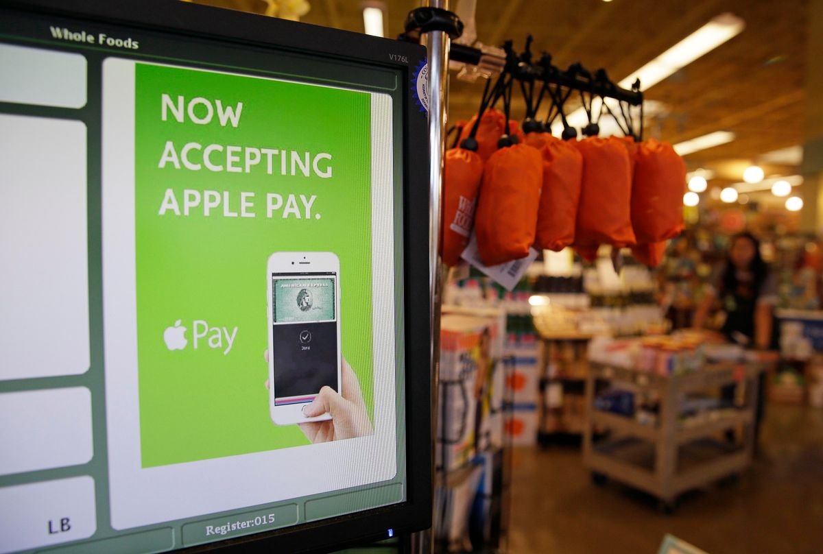 In this photo taken Friday, Oct. 17, 2014, a cash register terminal promotes usage of the new Apple Pay mobile payment system at a Whole Foods store in Cupertino, Calif. The new system launches on Monday. (AP Photo/Eric Risberg) (AP)
