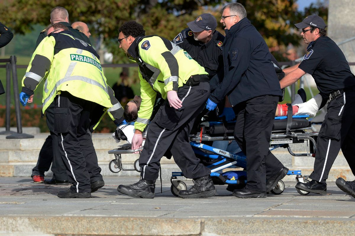 Paramedics and police pull a victim away from the Canadian War Memorial in Ottawa, Ontario, on Wednesday, Oct. 22, 2014. (AP Photo/The Canadian Press, Adrian Wyld)   (AP)