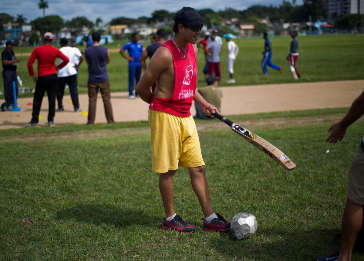 In this Sept. 24, 2014 photo, a cricket player waits his turn to play next to a soccer ball in Havana, Cuba, Monday, Sept. 29, 2014. Without a national tournament, Cuba has amateur tournaments  between Cuban teams and teams of students from cricket-playing countries. (AP Photo/Ramon Espinosa) (AP)