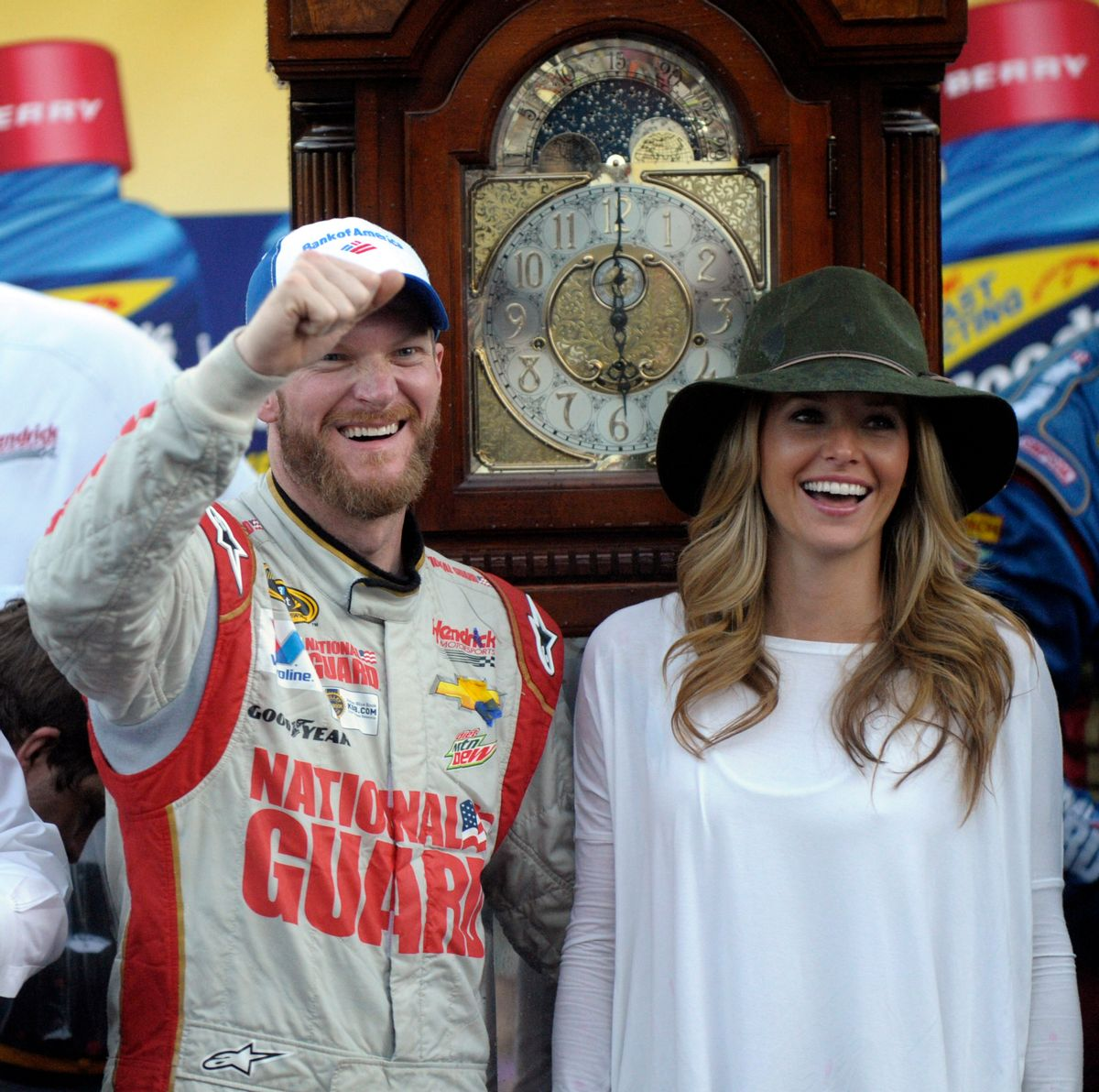 Dale Earnhardt Jr., left, and his girlfriend Amy Reimann, right, celebrate after he won the NASCAR Sprint Cup Series auto race at Martinsville Speedway in Martinsville, Va., Sunday, Oct. 26, 2014. The grandfather clock, background, is the winner's trophy. (AP Photo/Don Petersen) (AP)