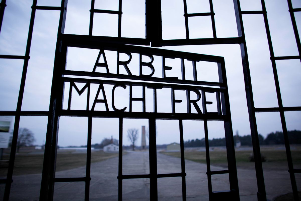 FILE - This Jan. 27, 2012, file photo shows the words 'Arbeit Macht Frei' (Work Sets You Free) at the main entrance of the Sachsenhausen Nazi concentration camp on the international Holocaust remembrance day in Oranienburg, Germany. An Associated Press investigation found dozens of suspected Nazi war criminals and SS guards collected millions of dollars in Social Security payments after being forced out of the United States.  (AP/Markus Schreiber)