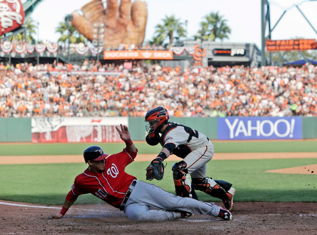 Washington Nationals Wilson Ramos (40) scores past the tag of San Francisco Giants catcher Buster Posey in the seventh inning during Game 3 of baseball's NL Division Series in San Francisco, Monday, Oct. 6, 2014.(AP Photo/Marcio Jose Sanchez) (AP)