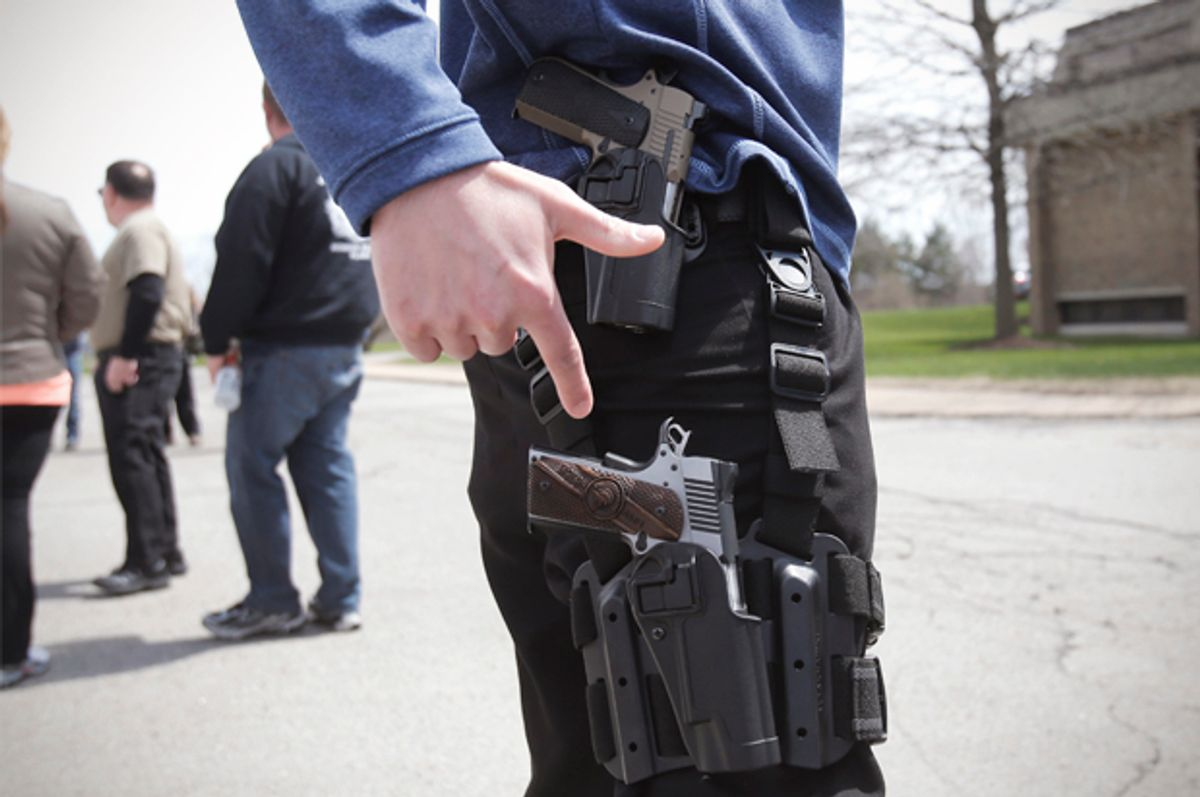 A gun rights supporter openly carries two pistols strapped to his leg during a rally in support of the Michigan Open Carry gun law in Romulus, Michigan April 27, 2014.        (Reuters/Rebecca Cook)