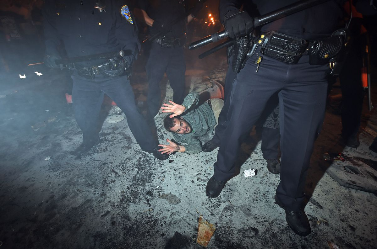 San Francisco police officers subdue a man who was seen driving a meter maid vehicle through the Mission district after the San Francisco Giants won the World Series baseball game against the Kansas City Royals on Wednesday, Oct. 29, 2014, in San Francisco.  There were several reports of fires being set and violence breaking out after the Giants win. (AP Photo/Noah Berger) (AP)