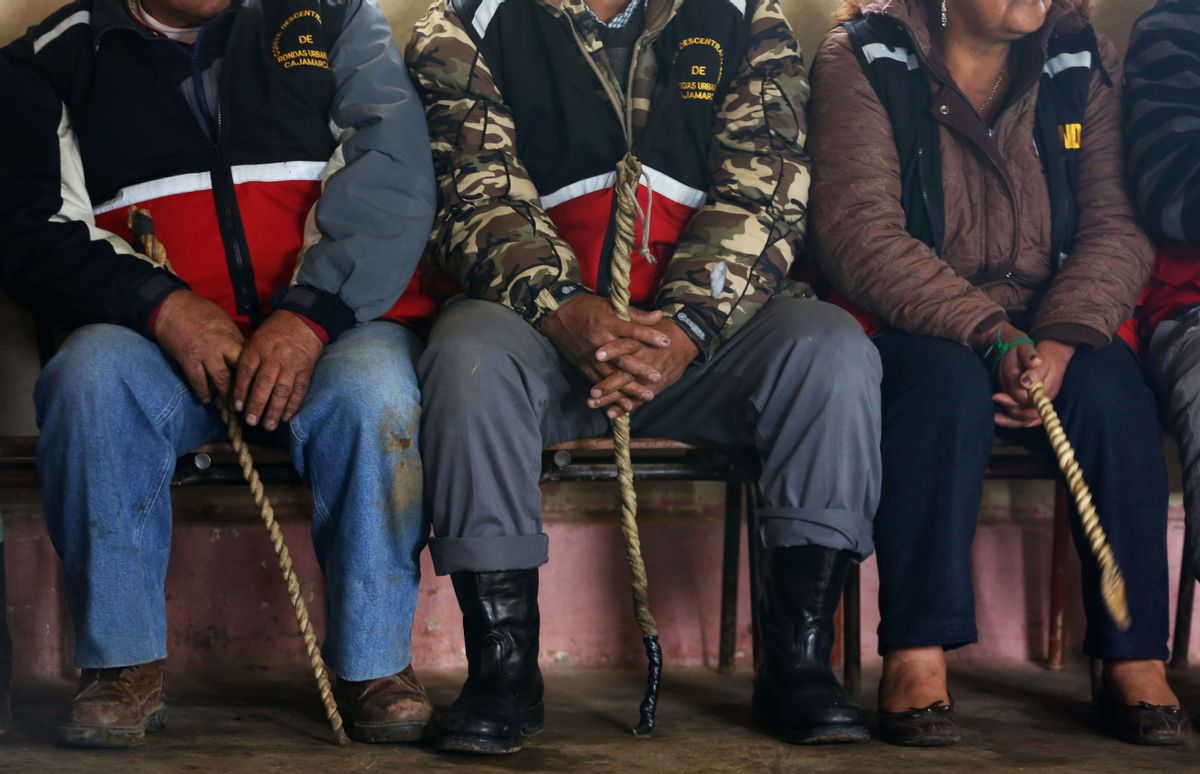 """In this May 9, 2014 photo, men and women, all wearing citizen patrol vests and wielding whips, take part in a hearing of an accused community member, in the Cajamarca municipality, Santa Rosa de Chumbil, Peru. For all but the most serious crimes, this is how justice is routinely administered in this highlands provincial capital of 200,000 people: self-appointed bands of vigilantes known as """"rondos urbanas,"""" or urban patrols, take on the roles of police, prosecutors and judges. (AP Photo/Martin Mejia) (AP)"""