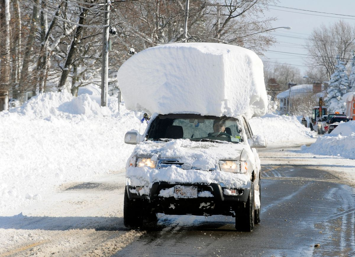 A vehicle, with a large chunk of snow on its top, drives along Route 20 after digging out after a massive snow fall in Lancaster, N.Y. Wednesday, Nov. 19, 2014. Another two to three feet of snow is expected in the area. (AP Photo/Gary Wiepert) (AP)