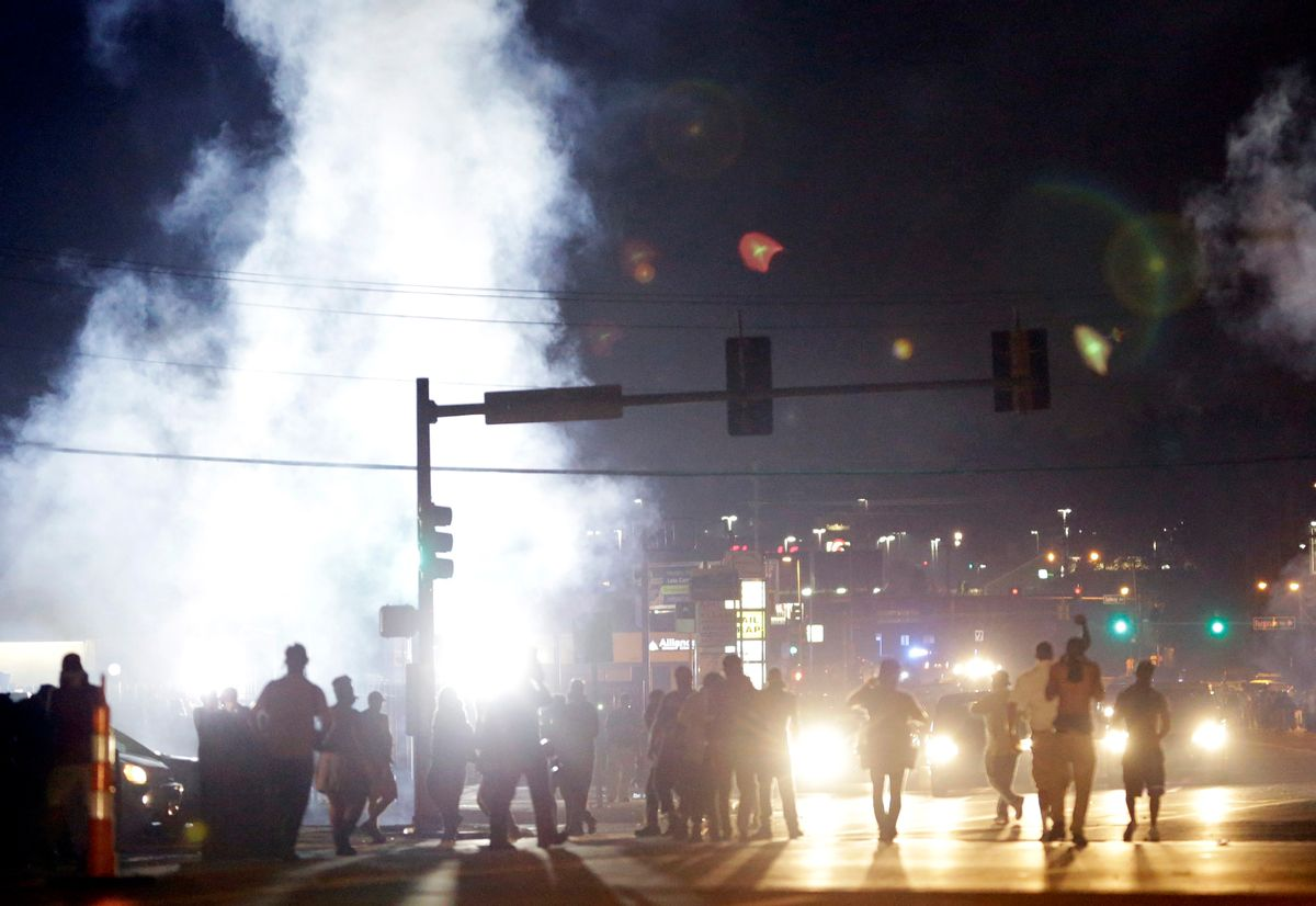 In this Monday, Aug. 18, 2014 file photo, people stand near a cloud of tear gas in Ferguson, Mo. during protests for the Aug. 9 shooting of unarmed black 18-year-old Michael Brown by a white police officer. The U.S. government agreed to a police request to shut down several miles of airspace surrounding Ferguson, even though authorities said their purpose was to keep media helicopters away during protests in August, according to recordings of air traffic control conversations obtained by The Associated Press.    (AP Photo/Jeff Roberson)