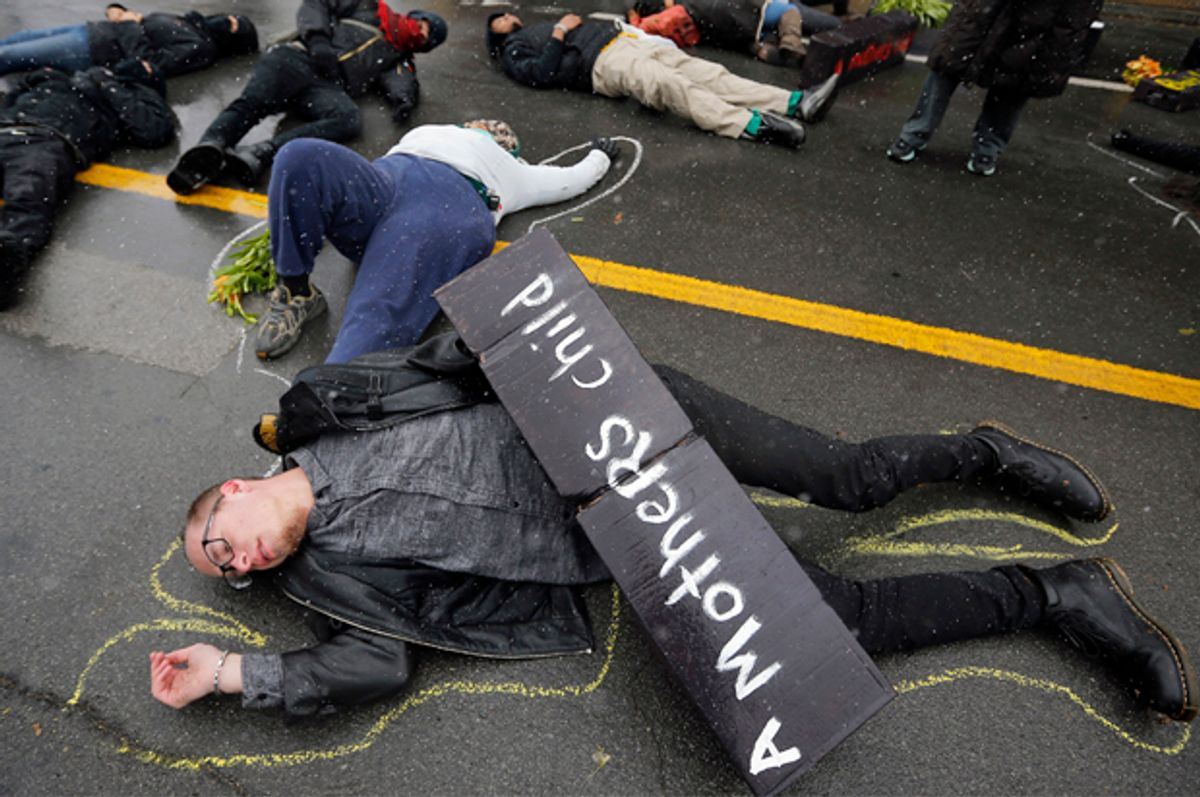 Demonstrators lie on the ground during a protest marking the 100th day since the shooting death of Michael Brown in St. Louis, Missouri November 16, 2014.            (Reuters/Jim Young)