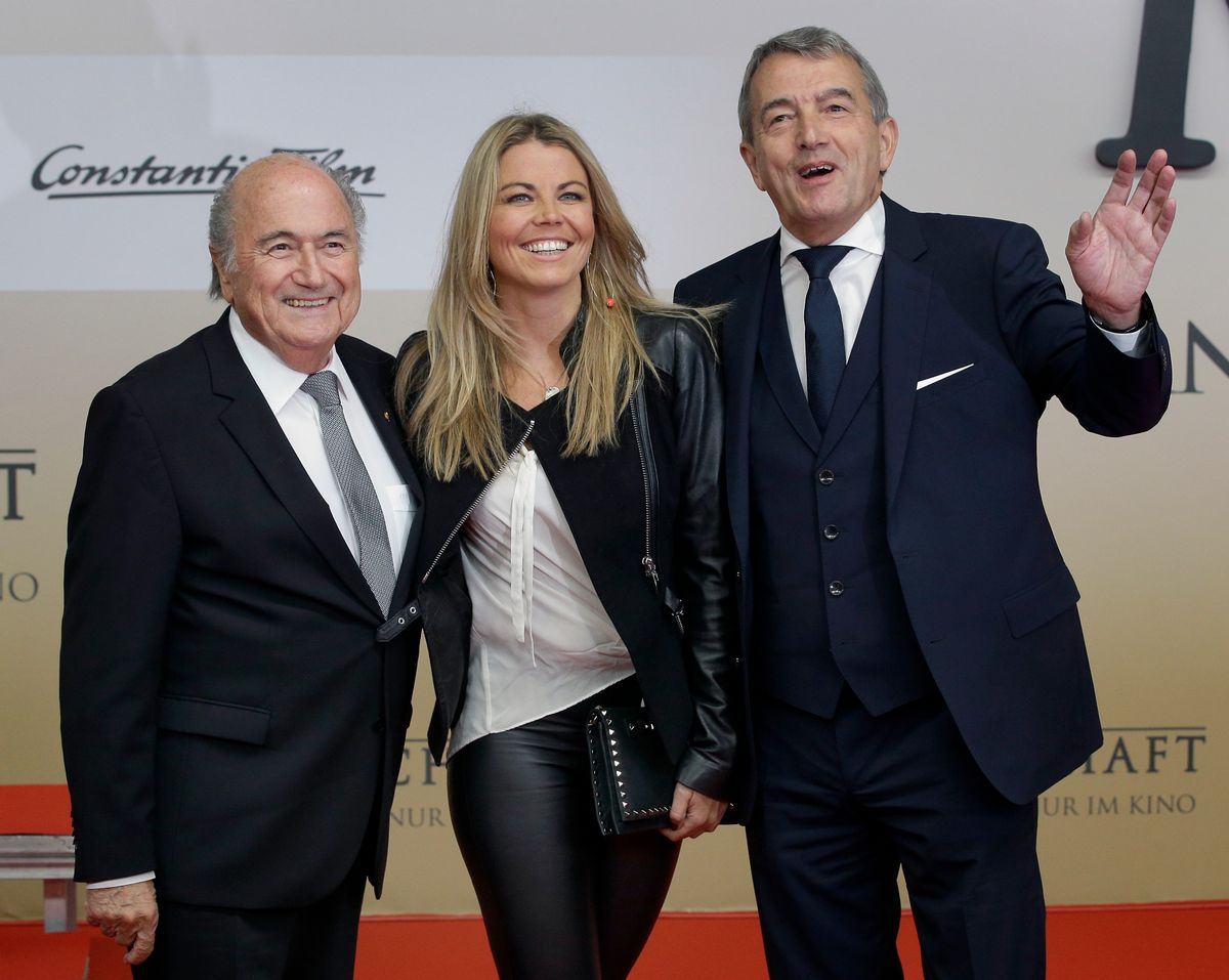 Wolfgang Niersbach, President of the German Soccer Association (DFB), right, FIFA President Sepp Blatter, left, and Niersbach's partner Marion Popp, center, pose for the media as they arrive for the premiere of the movie 'Die Mannschaft' (The Team) in Berlin, Germany, Monday, Nov. 10, 2014. (AP Photo/Michael Sohn) (AP)