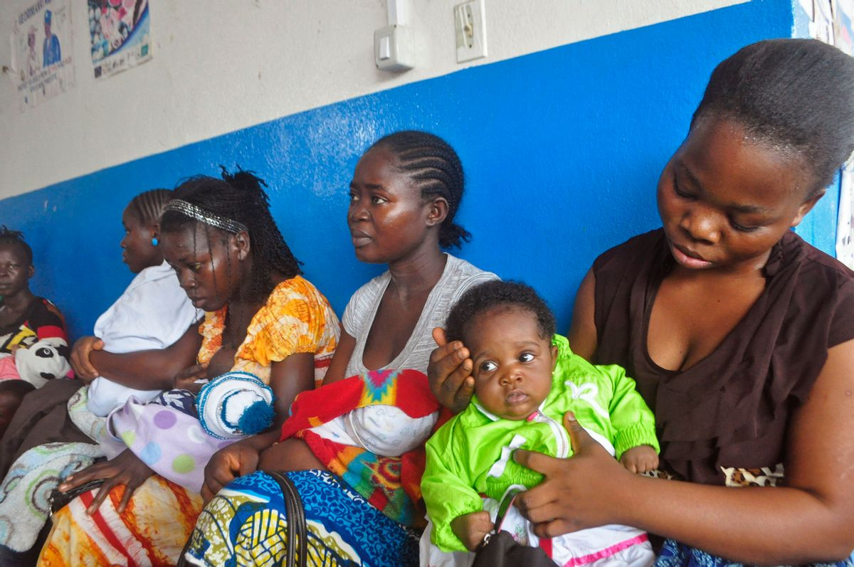 """In this photo taken on Monday, Nov. 3, 2014,  mothers wait inline for their children to be vaccinated by heath workers at the Pipeline Community Health Center, situated on the outskirts of  Monrovia, Liberia.  The Ebola outbreak has spawned a """"silent killer,"""" experts say: hidden cases of malaria, pneumonia, typhoid and the like that are going untreated because people in the countries hardest hit by Ebola either cannot find an open clinic or are too afraid to go to one. (AP/Abbas Dulleh)"""