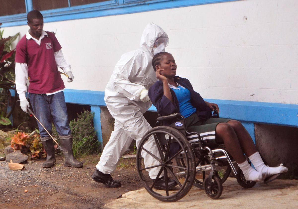 """In this photo taken on Saturday, Nov. 1, 2014,  a woman prisoner suspected of suffering from the Ebola virus, from Tubmanburg central prison, is pushed in a wheelchair towards a medical vehicle,  to be taken to an Ebola treatment center in Monrovia, Liberia. The Ebola outbreak has spawned a """"silent killer,"""" experts say: hidden cases of malaria, pneumonia, typhoid and the like that are going untreated because people in the countries hardest hit by Ebola either cannot find an open clinic or are too afraid to go to one. (AP Photo/ Abbas Dulleh)  (AP)"""