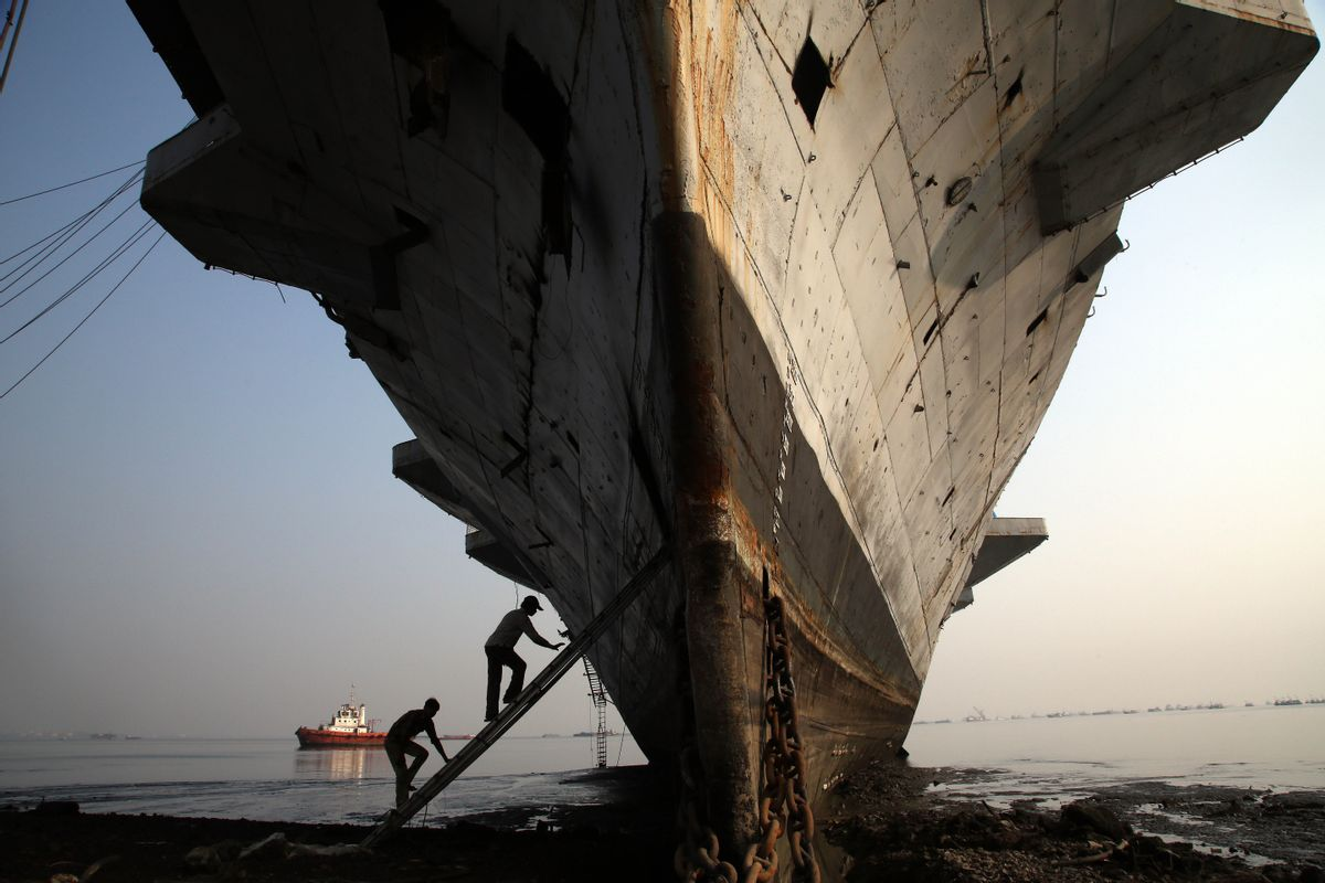 Workers climb to enter India's first aircraft carrier INS Vikrant to dismantle it at a ship-breaking yard in Mumbai, India, Saturday, Nov. 22, 2014. The iconic naval vessel, that was purchased from Britain in 1957, played a key role during the India-Pakistan war of 1971 and was decommissioned in 1997. (AP Photo/Rajanish Kakade) (AP)