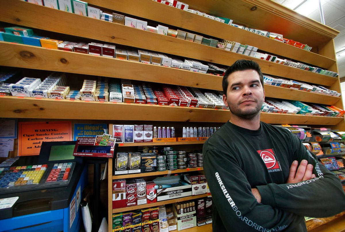 Brian Vincent poses in front of a large display of tobacco products at Vincent's Country Store in Westminster, Mass., Thursday, Nov. 6, 2014. Local officials are contemplating what could be a first: a blanket ban on all forms of tobacco and e-cigarettes, leaving some shop owners fuming. (AP Photo/Elise Amendola)   (AP/Elise Amendola)