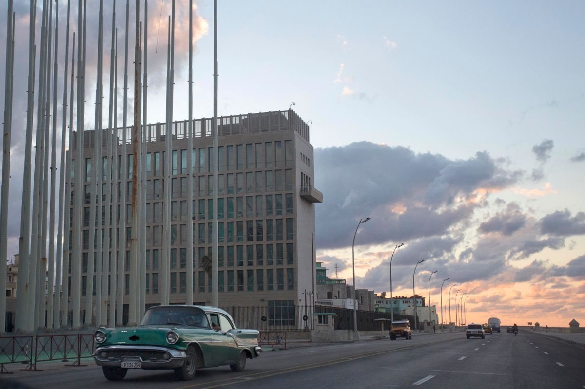 """An American classic car passes next to the building of the US Interests Section in Havana, Cuba, Wednesday, Dec. 17, 2014.  President Barack Obama announced the re-establishment of diplomatic relations as well as an easing in economic and travel restrictions on Cuba Wednesday, declaring an end to America's """"outdated approach"""" to the island in a historic shift that aims to bring an end to a half-century of Cold War enmity.(AP Photo/Desmond Boylan) (AP)"""