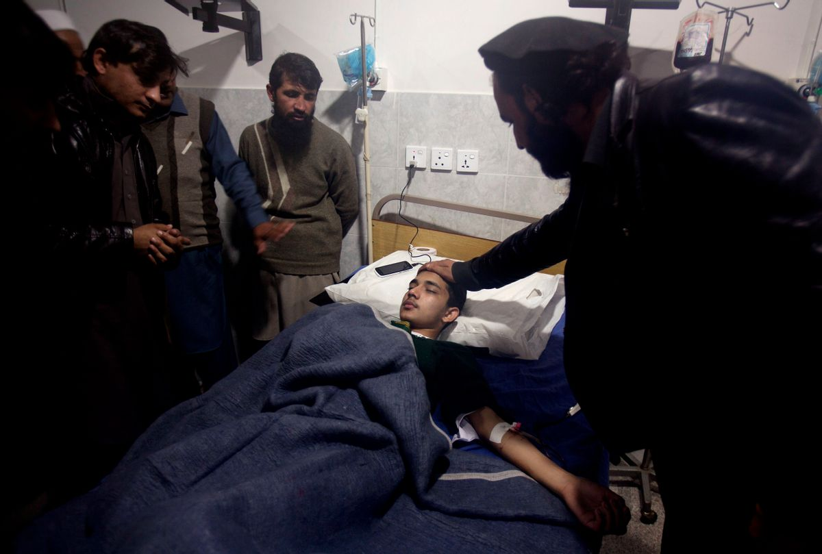 A man comforts a child who survives a Taliban attack on a school that killed more than 100 people, admits at a local hospital in Peshawar, Pakistan, Tuesday, Dec. 16, 2014. Taliban gunmen stormed a military-run school in the northwestern Pakistani city of Peshawar on Tuesday, killing at least 100 people, mostly children, before Pakistani officials declared a military operation to clear the school over. (AP Photo/B.K. Bangash) (AP)