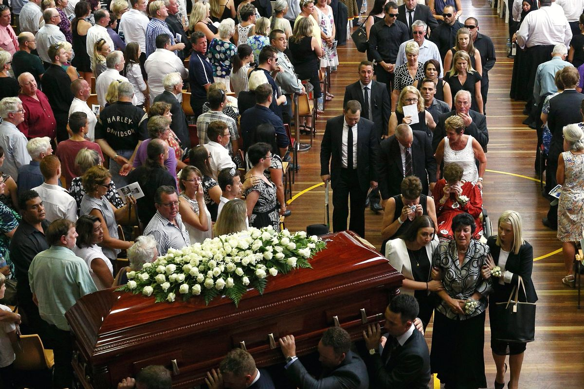 The coffin of Phillip Hughes is carried down the aisle as his mother, Virginia Hughes, second right at bottom, is comforted during his funeral in Macksville, Australia, Wednesday, Dec. 3, 2014. Hughes died last Thursday, two days after he was hit in the head during a domestic cricket match. (AP Photo/Cameron Spencer, Pool) (Cameron Spencer)