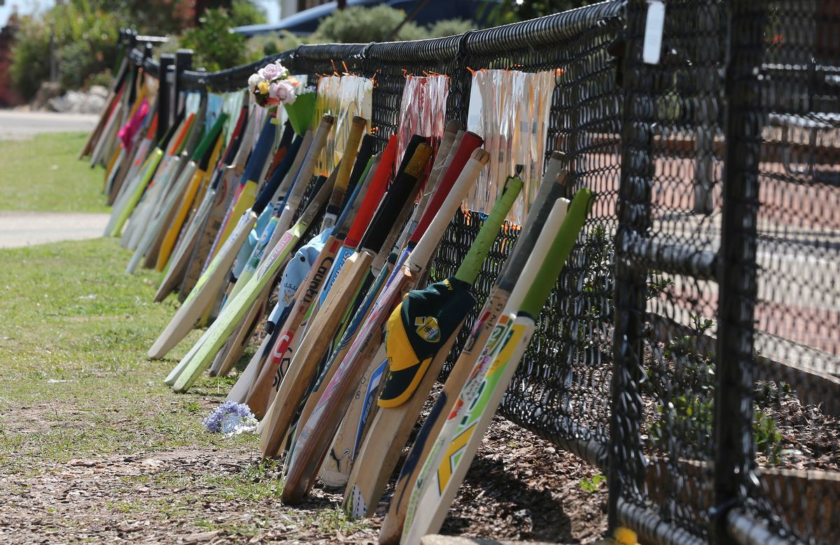Cricket bat stand as tribute outside a primary school during the funeral of Australian cricketer Phil Hughes in Macksville, Australia, Wednesday, Dec. 3, 2014. Hughes, 25,  died last Thursday, two days after he was hit in the head during a domestic cricket match.(AP Photo/Rob Griffith) (AP)