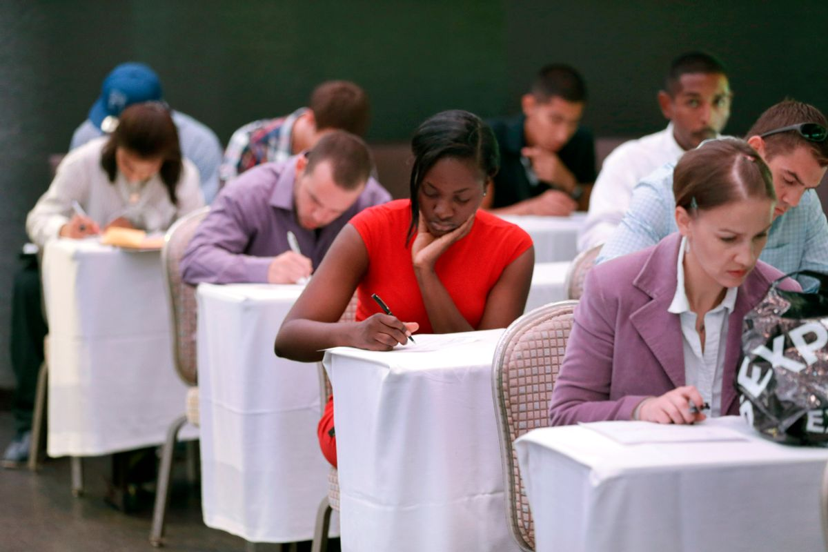 In this Monday, Oct. 6, 2014 photo, job seekers fill out forms before being interviewed during a job fair at Fontainebleau Miami Beach in Miami Beach, Fla. (AP/Wilfredo Lee)
