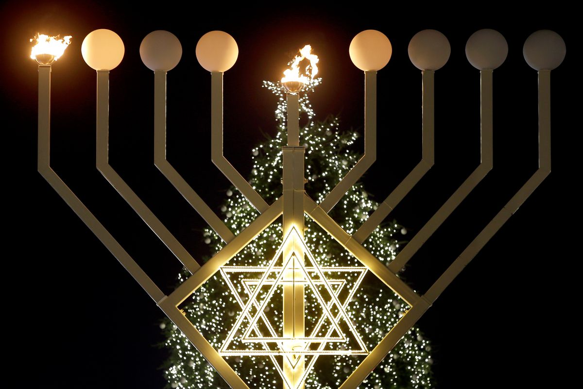 FILE - In this Tuesday, Dec. 16, 2014 file photo, the first flames of a a giant Hanukkah Menorah in front of a Christmas tree at the Brandenburg Gate in Berlin, Germany, burn at the launch of the eight-day Jewish Festival of Lights, named Hanukkah. The lights were inflamed by German Interior Minister Thomas de Maiziere and Rabbi Yehuda Teichtal. (AP Photo/Michael Sohn, File) (AP)