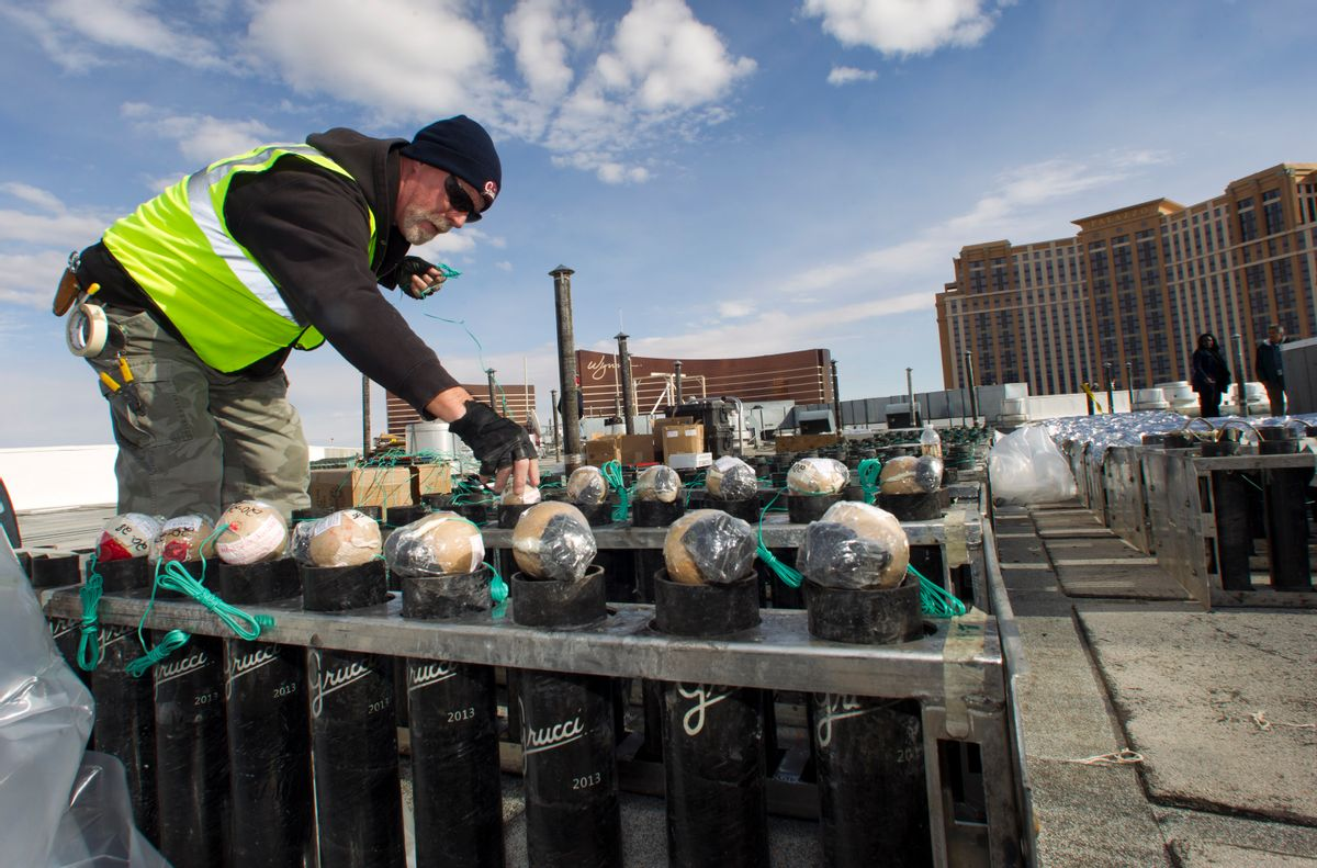 Pyrotechnician Henry Herman loads aerial shells during New Years Eve fireworks preparation on the roof of the Treasure Island hotel-casino in Las Vegas, Tuesday, Dec. 30, 2014. The Fireworks by Grucci show will explode from the rooftops of seven casinos. (AP Photo/Las Vegas Sun, Steve Marcus) (AP)
