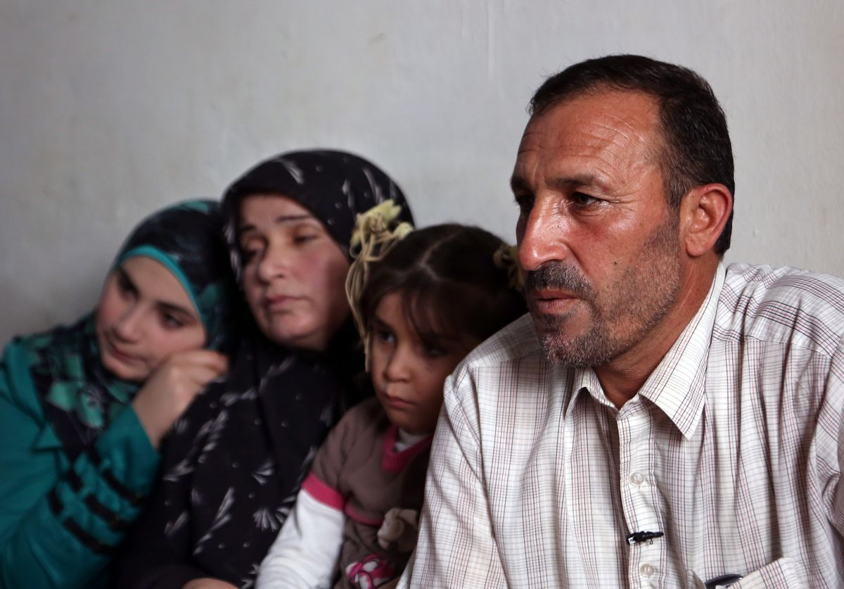 In this Thursday, Nov. 20, 2014 photo, Mohammed Aloun, 43, right, speaks during an interview with The Associated Press as he sits with his family at their house in the northern port city of Tripoli, Lebanon. The Alouns are one of several Syrian families who were given asylum in Uruguay after its government offered to accept 120 refugees. It's a small number compared to the 3 million Syrians who have fled the conflict, now in its fourth year, crowded into overwhelmed neighboring countries or who tried to reach Europe. (AP Photo/Bilal Hussein) (AP)