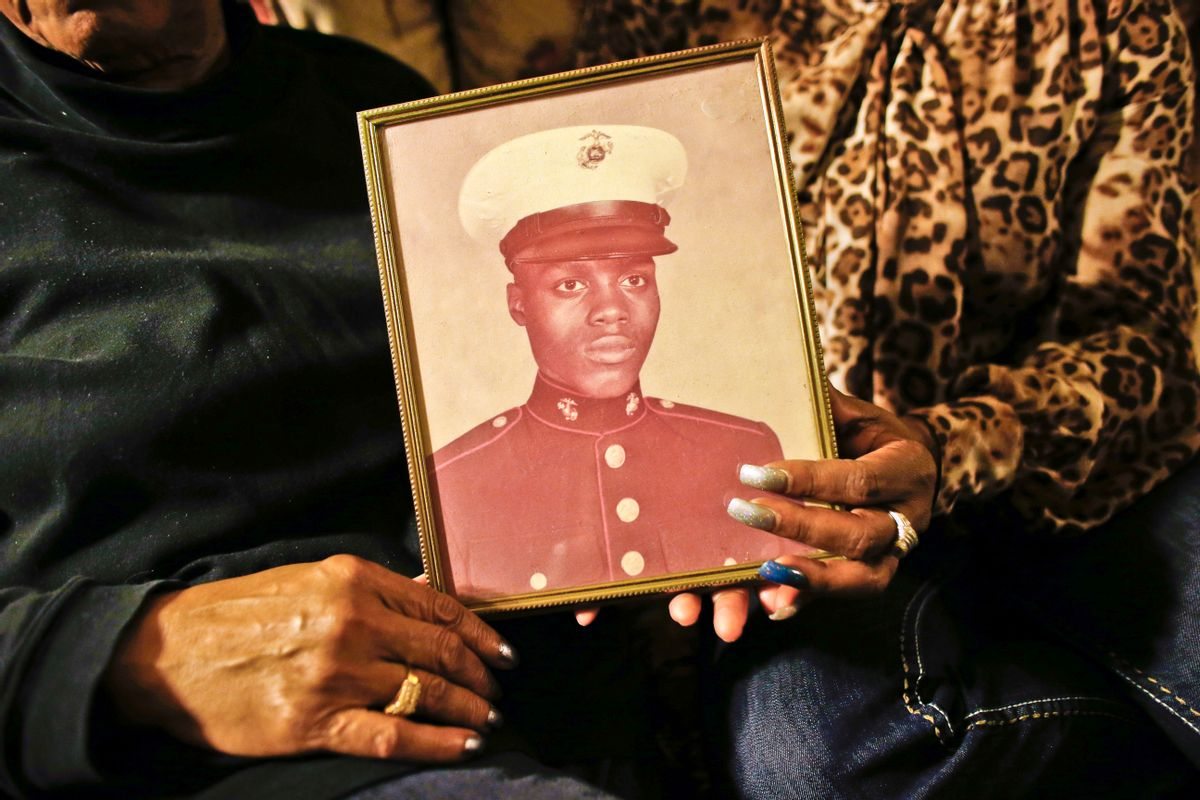 FILE - In this March 12, 2014 file photo, a picture of Jerome Murdough, a former homeless Marine who died in a mental observation unit on Rikers Island jail on Feb. 15, is held by his mother Alma Murdough left, and sister Cheryl Warner at Alma Murdough's home in the Queens borough of New York. New York Mayor Bill de Blasio plans to announce his $130 million, four-year plan to overhaul how the nation's most populous city deals with mentally ill and drug-addicted suspects, diverting many to treatment instead of jail.  (AP Photo/Jason DeCrow, File) (AP)