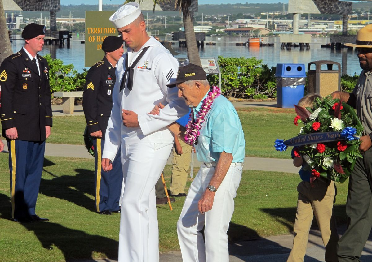 A Navy sailor escorts Navy veteran and Pearl Harbor survivor John Chapman during a ceremony to mark the 73rd anniversary of the Japanese attack on Pearl Harbor, Sunday, Dec. 7, 2014, at Pearl Harbor, Hawaii. The attack launched the U.S. into World War II. (AP Photo/Jennifer Sinco Kelleher) (AP)