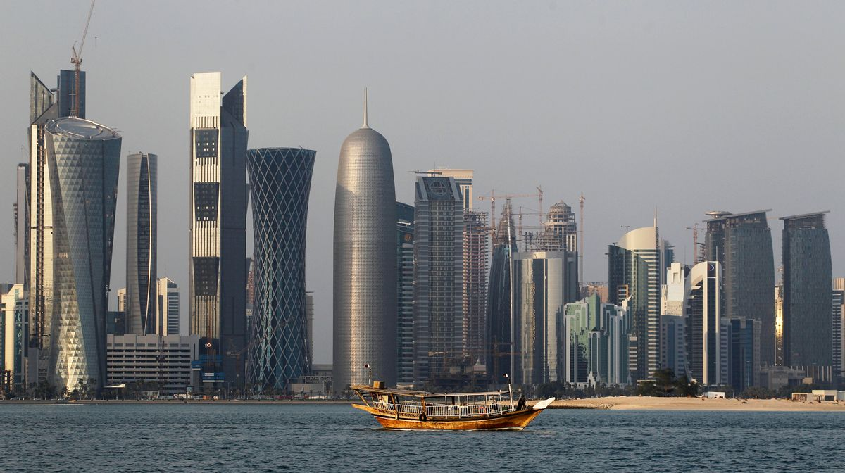FILE - In this Thursday Jan. 6, 2011 file photo, a traditional dhow floats in the Corniche Bay area with tall buildings of the financial district in the background. The 2022 World Cup in Qatar, the wealthy oil- and gas-producing Gulf nation with giant look-at-me ambitions that belie its small size, is shaping up as a unique experience. (AP Photo/Saurabh Das, File) (AP Photo/Saurabh Das, File)