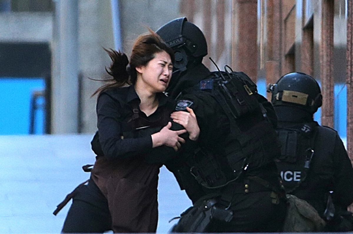 A hostage runs to armed tactical response police officers from a cafe under siege at Martin Place in Sydney, Australia, Dec. 15, 2014.         (AP/Rob Griffith)