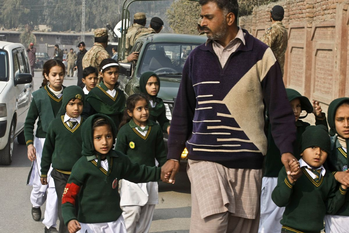 """A plainclothes security officer escorts students evacuated from a school as Taliban fighters attack another school nearby, killing148 people, mostly children, in Peshawar, Pakistan, Tuesday, Dec. 16, 2014. U.S. Secretary of State John Kerry condemned the attacks: """"Mothers and fathers send their kids to school to learn and to be safe and to dream and to find opportunity. And particularly at this military school in Pakistan, they sent their kids there with the hope and dreams of serving their country. Instead, today they are gone, wiped away by Taliban assassins who serve a dark and almost medieval vision, and the opposite of everything that those mothers and fathers wanted for their children."""" (AP Photo/Mohammad Sajjad) (AP)"""