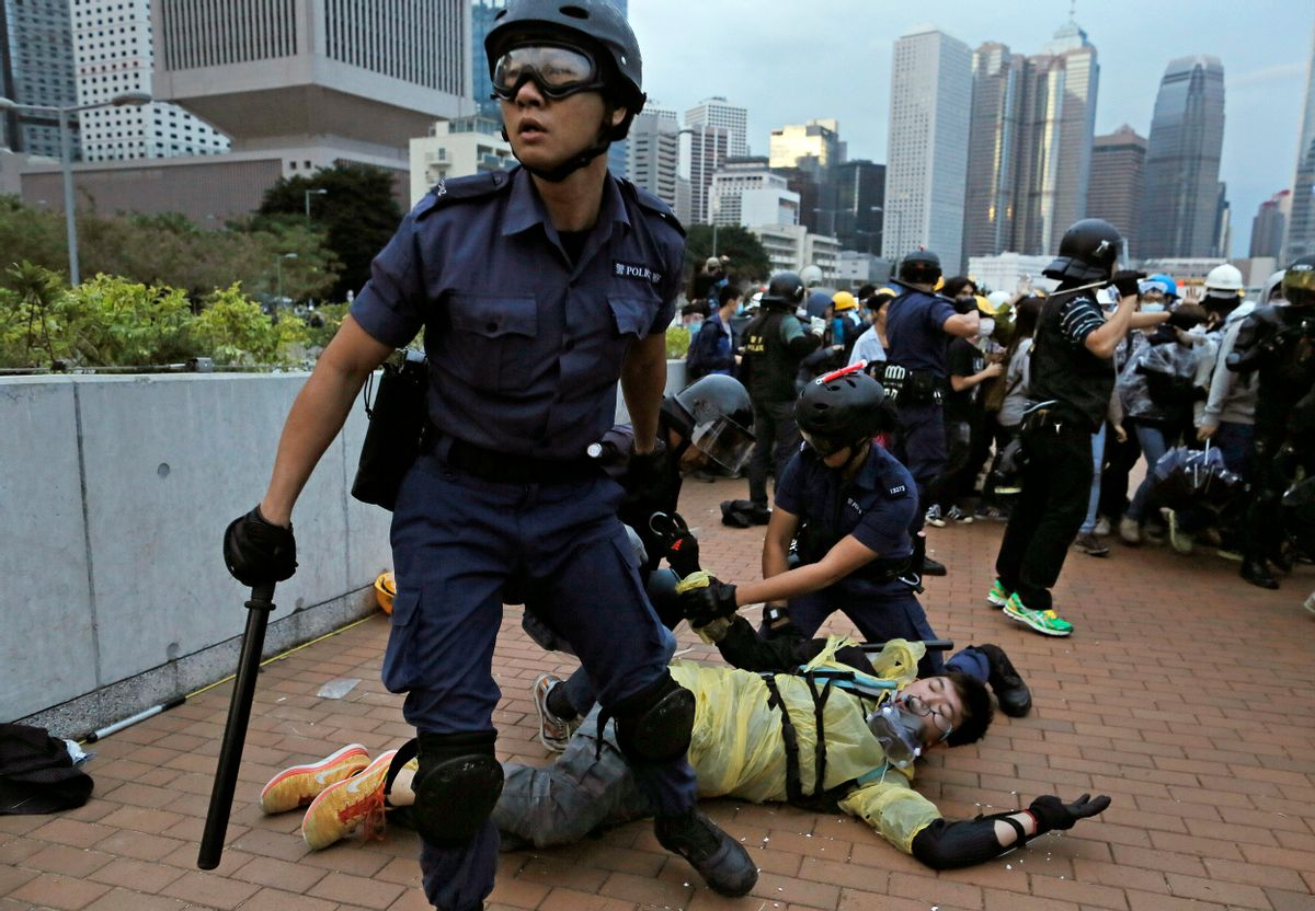 A protester is arrested by police officers outside government headquarters in Hong Kong Monday, Dec. 1, 2014. Pro-democracy protesters clashed with police as they tried to surround Hong Kong government headquarters late Sunday, stepping up their movement for genuine democratic reforms after camping out on the city's streets for more than two months. (AP Photo/Vincent Yu) (Vincent Yu)