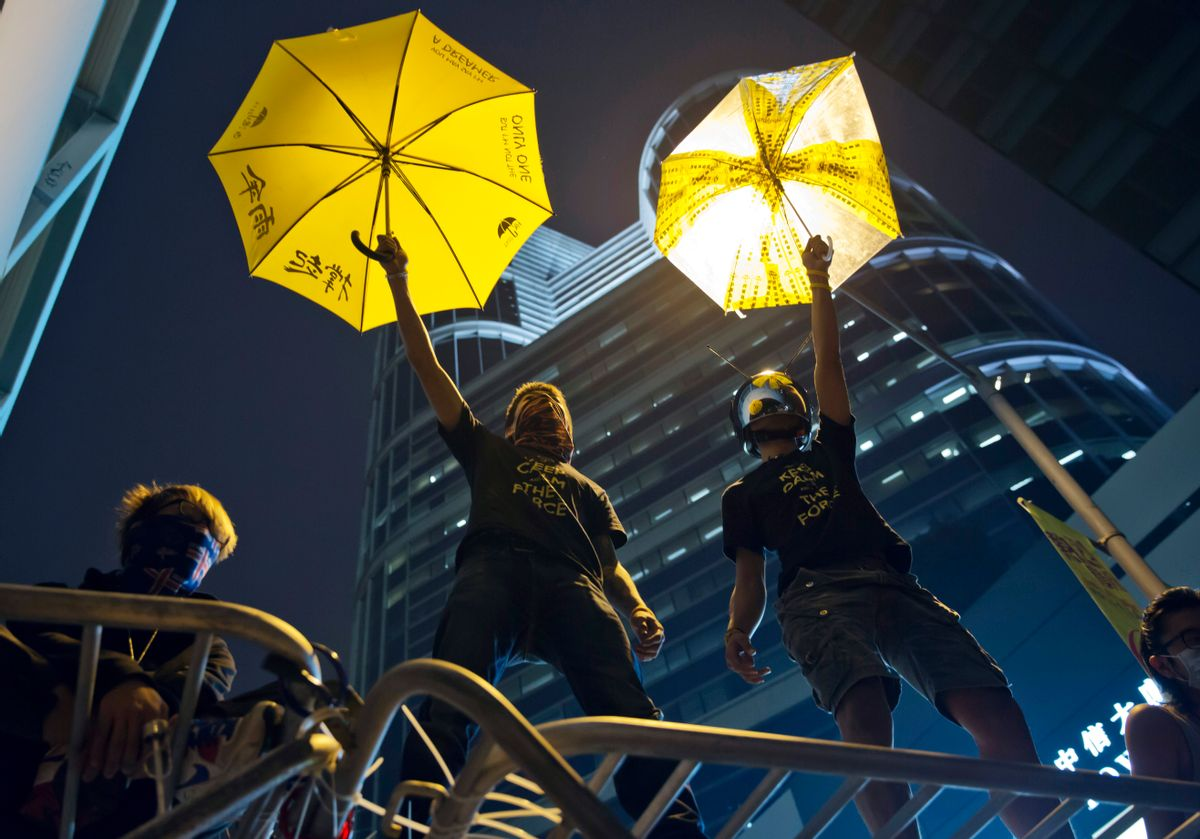 Protesters pose for photographs on a barricade at the occupied area outside government headquarters in Hong Kong Wednesday, Dec. 10, 2014. Hong Kong's dwindling number of pro-democracy protesters vowed Wednesday to stay until the last minute before authorities clear them off a highway where they've been camped out for more than two months. (AP Photo/Kin Cheung) (Kin Cheung)