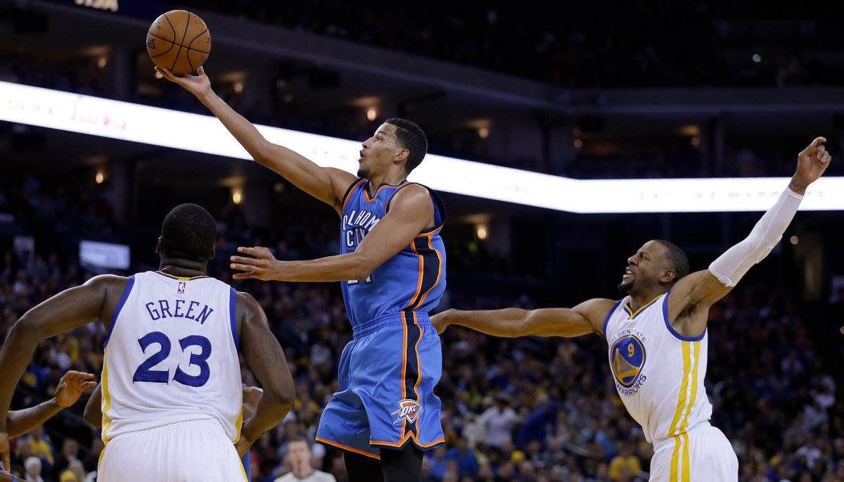 Oklahoma City Thunder guard Andre Roberson lays up a shot between Golden State Warriors' Draymond Green (23) and Andre Iguodala during the second half of an NBA basketball game Thursday, Dec. 18, 2014, in Oakland, Calif. The Warriors won 114-109. (AP Photo/Ben Margot) (AP)
