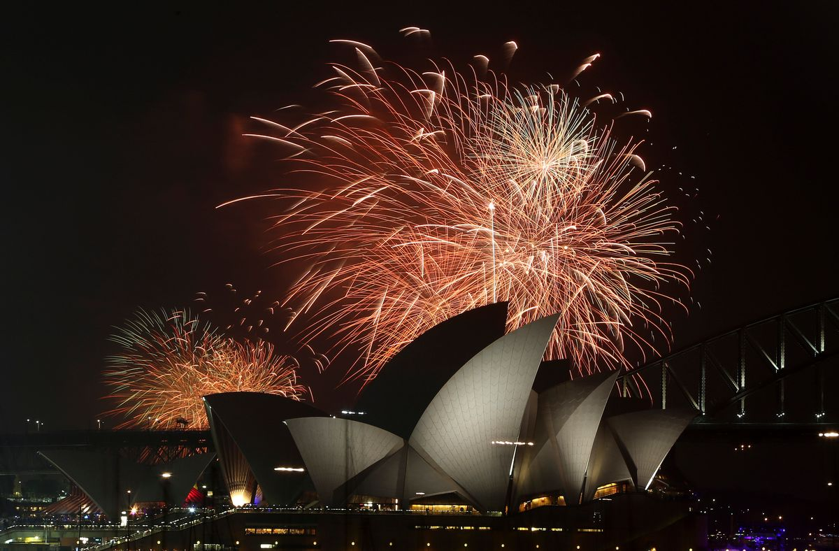 Fireworks explode over the Opera House and the Harbour Bridge during pre-New Years Eve  celebrations in Sydney, Australia, Wednesday, Dec. 31, 2014. Thousands of people crammed into Lady Macquaries Chair look-out to see the new year in and watch the annual fireworks show. (AP Photo/Rob Griffith) (Rob Griffith)