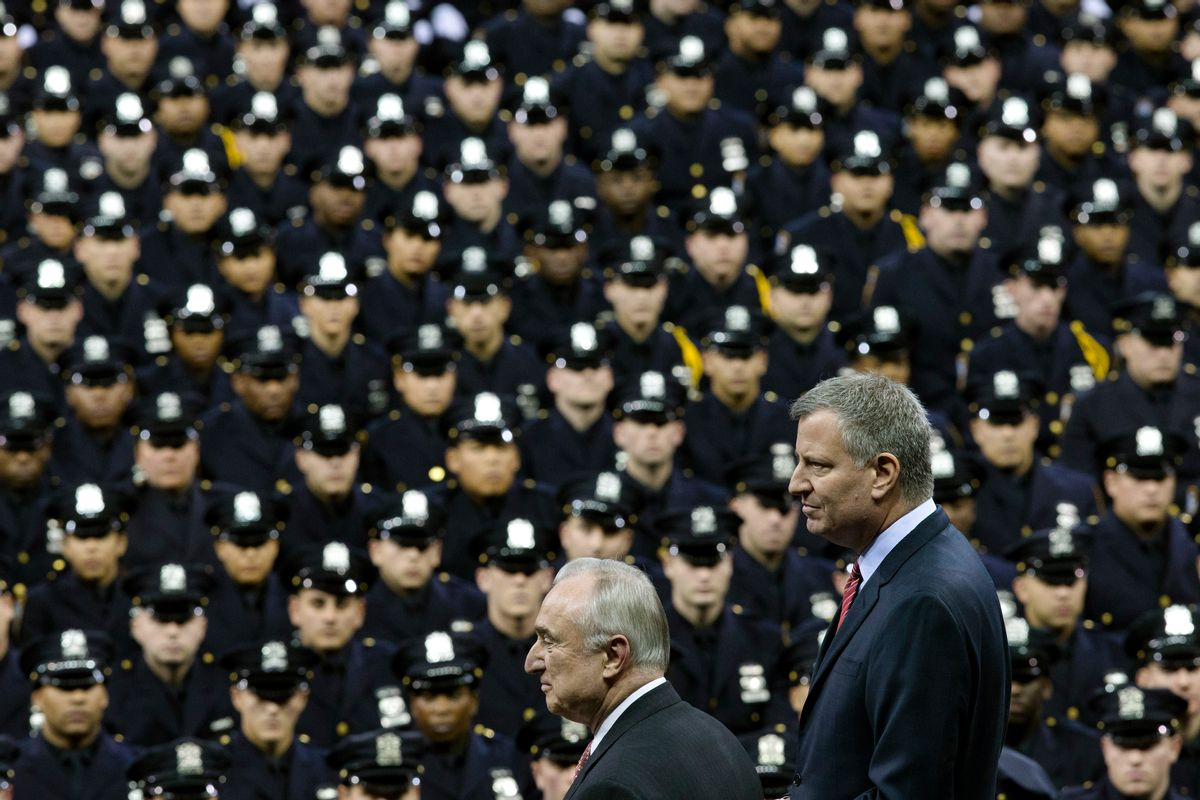 FILE - In this Monday, Dec. 29, 2014 file photo New York City Mayor Bill de Blasio, right, and NYPD police commissioner Bill Bratton, center, stand on stage during a New York Police Academy graduation ceremony at Madison Square Garden in New York.  (AP/John Minchillo)