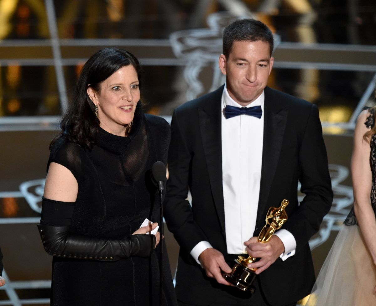 """Laura Poitras, left, and Glenn Greenwald accept the award for best documentary feature for """"Citizenfour"""" at the Oscars on Sunday, Feb. 22, 2015, at the Dolby Theatre in Los Angeles. (Photo by John Shearer/Invision/AP)   (John Shearer/invision/ap)"""